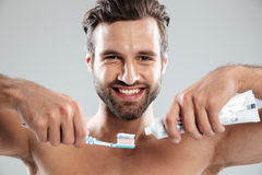 把牙膏放的一个微笑的人的画象在牙刷上 免版税库存图片