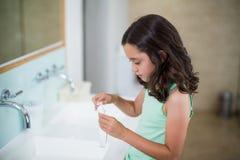 把牙膏放的女孩在刷子上在卫生间 库存图片