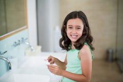 把牙膏放的女孩在刷子上在卫生间 免版税图库摄影