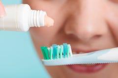 把牙膏放的妇女在牙刷上 免版税库存照片