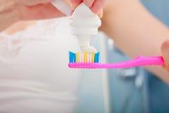 把牙膏放的妇女手在牙刷上 库存照片