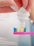 把牙膏放的妇女手在牙刷上 免版税库存照片