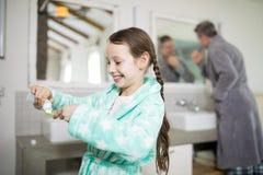 把牙膏放的微笑的女孩在牙刷上 免版税库存图片