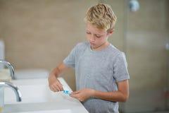把牙膏放的男孩在刷子上在卫生间 库存图片