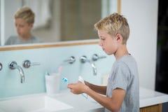 把牙膏放的男孩在刷子上在卫生间 库存照片
