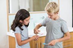 把牙膏放的男孩在姐妹牙刷上在卫生间 免版税库存照片