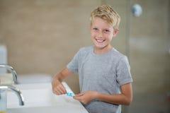 把牙膏放的男孩画象在刷子上在卫生间 免版税库存照片