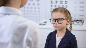 把玻璃放的女性医生在不悦的女孩,孩子上感到不安全,翻倒 股票视频