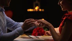 把珍贵的圆环放的男朋友在女性手指,体贴亲吻的夫妇上,礼物 股票视频