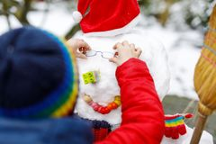 把眼睛玻璃放的小孩在雪人上 特写镜头 孩子获得与第一雪的乐趣在冬天 库存照片