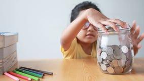把硬币放的亚裔小女孩入一个清楚的玻璃瓶子在桌隐喻挽救与声音精选的焦点的金钱概念在瓶子上 股票录像