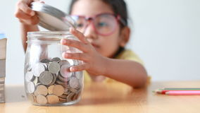 把硬币放的亚裔小女孩入一个清楚的玻璃瓶子在桌隐喻挽救与声音精选的焦点的金钱概念在瓶子上 影视素材