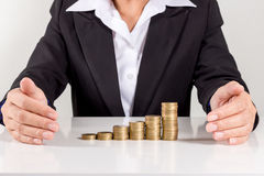 把硬币放的女实业家在堆金黄硬币上 免版税图库摄影
