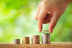 把硬币放的手在硬币堆上有绿叶被弄脏的背景 免版税图库摄影