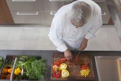 把红色和黄色喇叭花胡椒切成小方块的厨师 库存图片