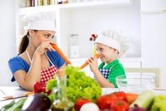 把红萝卜放在鼻子上和一起使用在k的母亲和儿子 免版税库存照片