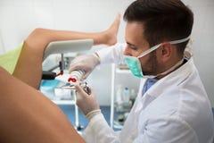 把胶凝体放的年轻妇产科医师在设备上对检查患者 免版税库存图片