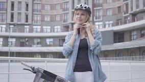 把自行车盔甲放在她的头上和骑她的自行车的俏丽的白肤金发的妇女以都市建筑学为背景 股票录像