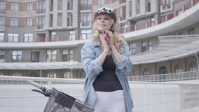 把自行车盔甲放在她的头上和骑她的自行车的画象俏丽的白肤金发的妇女以都市为背景 影视素材
