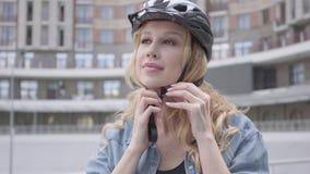 把自行车盔甲放在她的头上和骑她的自行车的画象逗人喜爱的白肤金发的妇女以都市为背景 股票视频