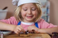 把葡萄干放的逗人喜爱的微笑的男孩在姜饼上 库存照片