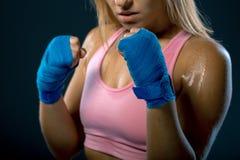 把装箱的愉快的微笑妇女 准备好少妇的战斗机战斗 坚强的妇女 在拳击绷带包裹的女性手 库存照片