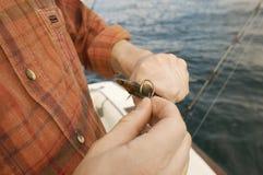 把诱饵放的人在钓鱼钩上 免版税库存图片