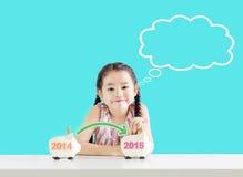 把金钱放的小女孩在存钱罐上与一个新年2015年 考虑挽救 库存图片