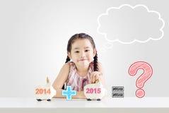 把金钱放的小女孩在存钱罐上与一个新年2015年 库存照片