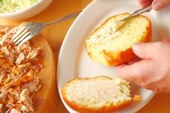 把马约角放在鸡肉三明治的小圆面包上 免版税图库摄影
