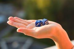 把1 4切成小方块在女性手,日落背景上 赌博的设备 库存照片