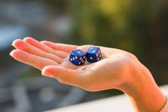 把1 2切成小方块在女性手,日落背景上 赌博的设备 库存图片