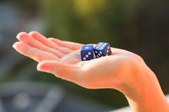 把1 6切成小方块在女性手,日落背景上 赌博的设备 免版税库存图片