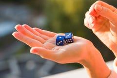 把1 3切成小方块在女性手,日落背景上 赌博的设备 库存图片
