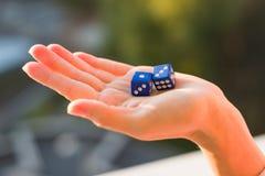 把1 3切成小方块在女性手,日落背景上 赌博的设备 免版税库存图片