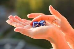 把1 1在女性手上,日落背景切成小方块 赌博的设备 免版税库存图片