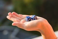把1 1在女性手上,日落背景切成小方块 赌博的设备 免版税库存照片