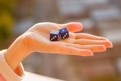 把1 1在女性手上,日落背景切成小方块 赌博的设备 图库摄影