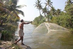 把他的网扔出去的渔夫 免版税库存图片