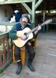 抒情诗人服装的一个人弹吉他在新生节日 免版税库存图片