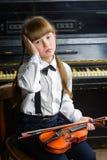 抓住她的头和拿着小提琴的烦乱或困厄的女孩 免版税库存图片
