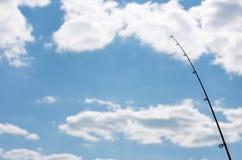抓住鱼 钓鱼竿的上部在蓝天背景的  库存照片