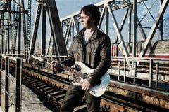 抓对照片人的作用有吉他的在铁路 免版税库存图片