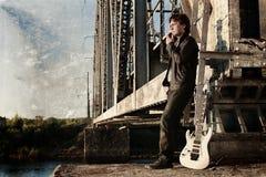 抓对照片人的作用有吉他的在铁路 免版税库存照片
