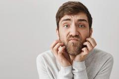 抓胡子的笨拙的不剃须的成人人特写镜头画象,当看与不满意的神色照相机,好象它时 库存图片