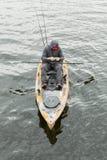 抓鱼的橙色皮船的人 他佩带一个黑敞篷 库存图片