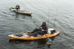抓鱼的橙色皮船的人 他佩带一个黑敞篷 库存照片
