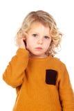抓他的头的哀伤的小男孩 免版税库存照片