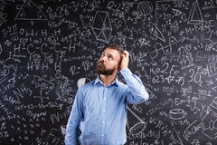 抓他的头的老师反对有mathemat的大黑板 免版税库存照片