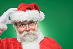 抓他的头的迷茫的圣诞老人 免版税库存图片